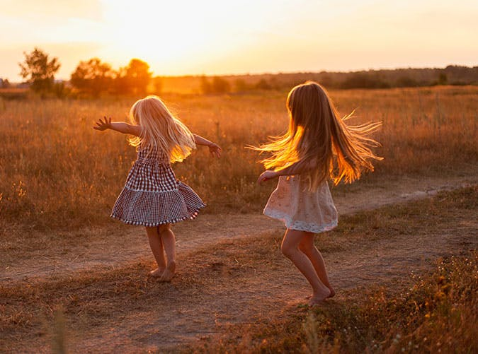 Two girls dancing outside in the field