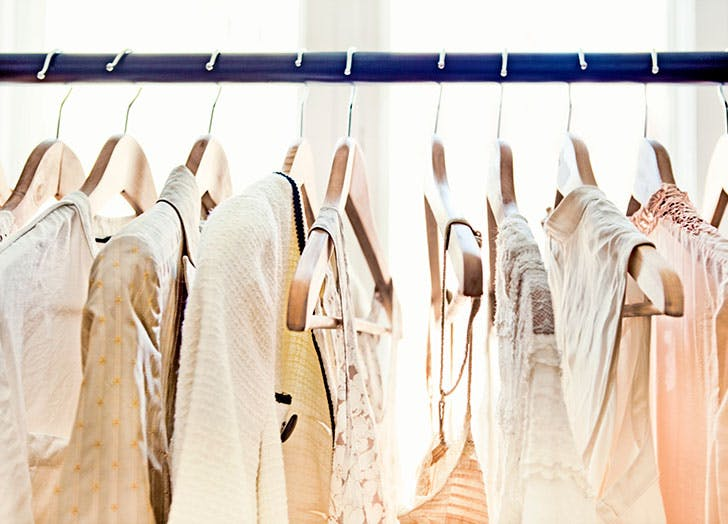 White and beige clothes hanging up in wardrobe