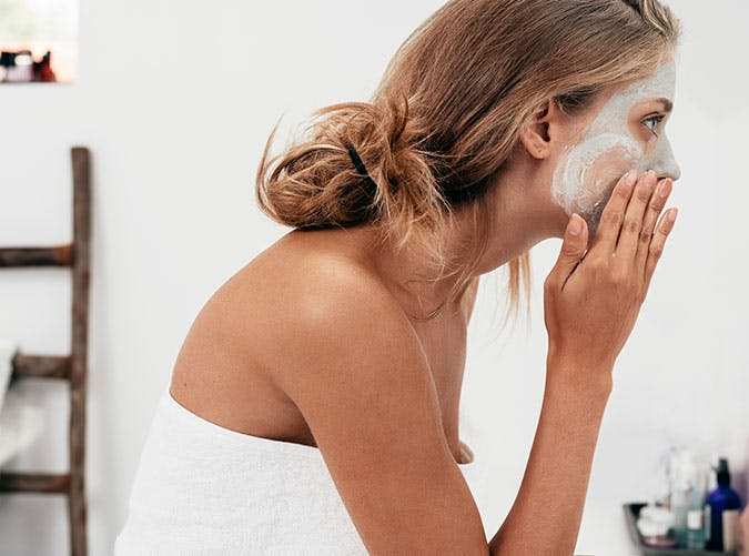 Woman putting on face mask for glowing skin