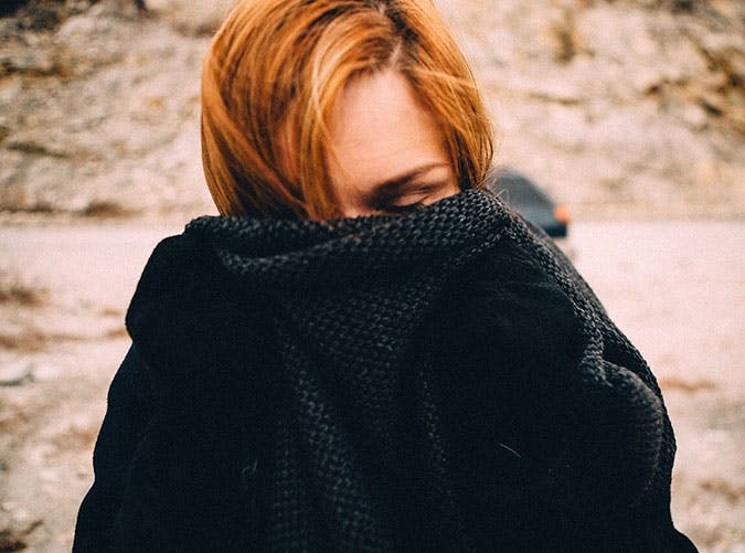 Woman with bright red hair hiding face in jumper