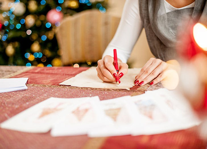 Woman writing thank you holiday card to teachers