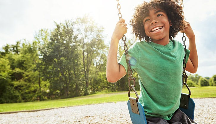 young boy playing on a swing at the park