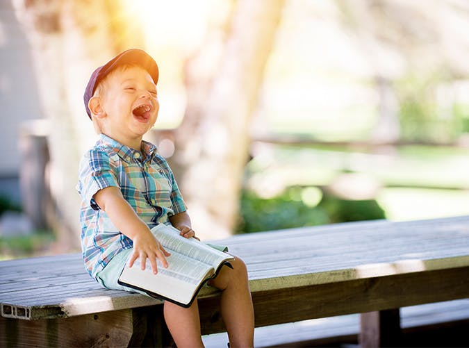 boy laughing reading book SLIDE