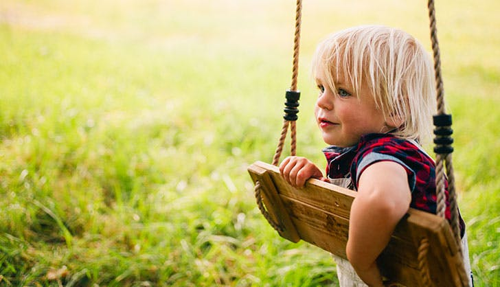 child plays with a swing at park
