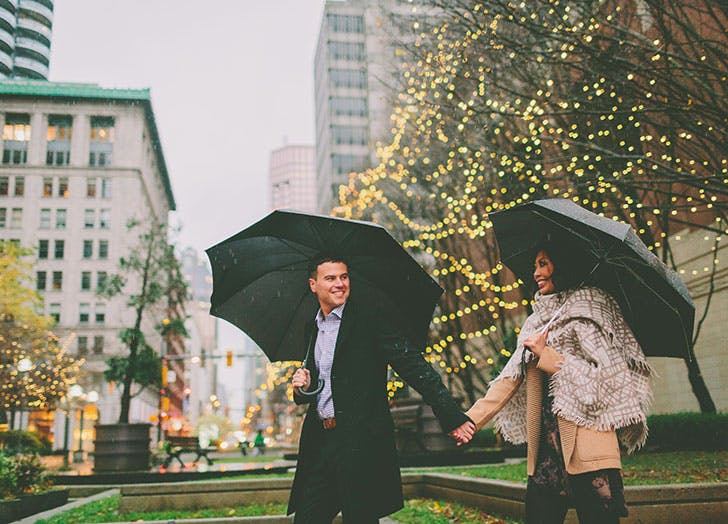 Couple holding hands and walking in the rain