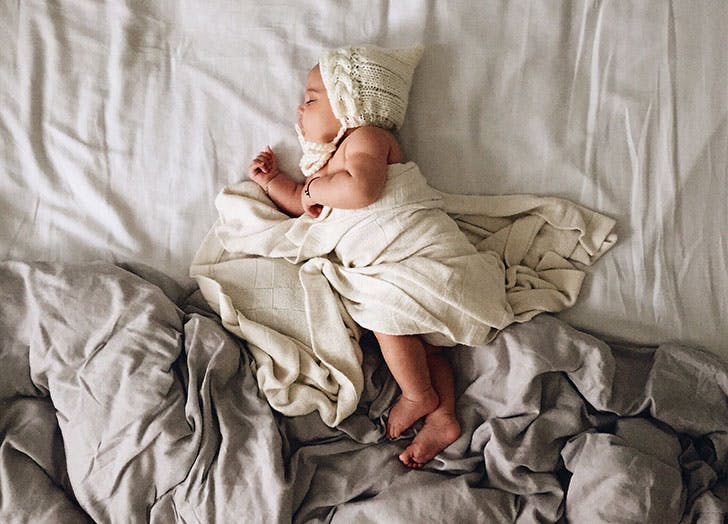 Cute baby lying in rumpled bed