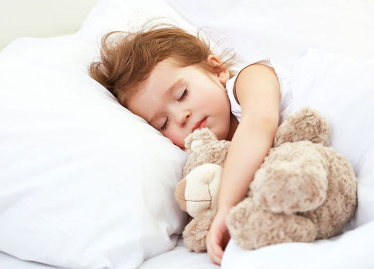 Cute little girl sleeping in bed