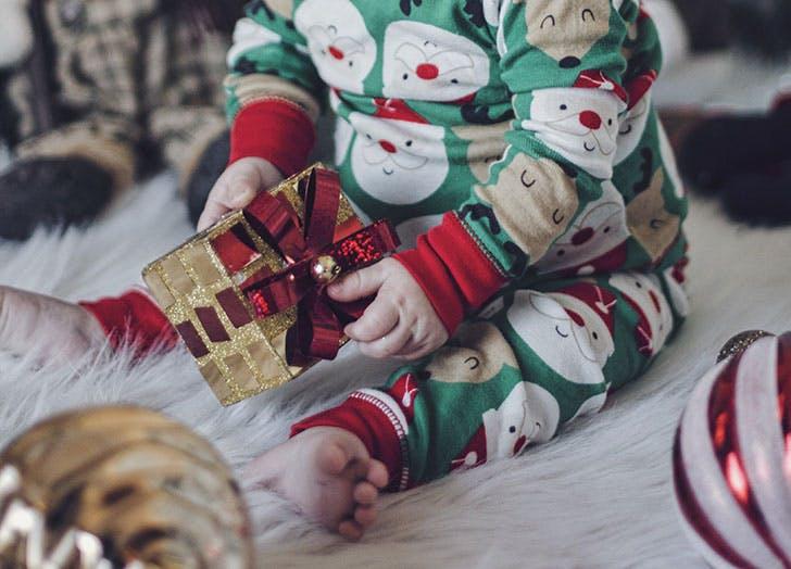 Kid in Santa pajamas unwrapping a Christmas gift
