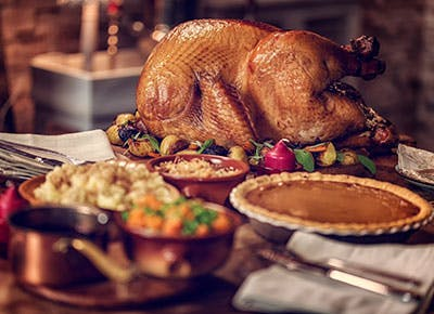 Perfectly cooked turkey and holiday sides on table 400