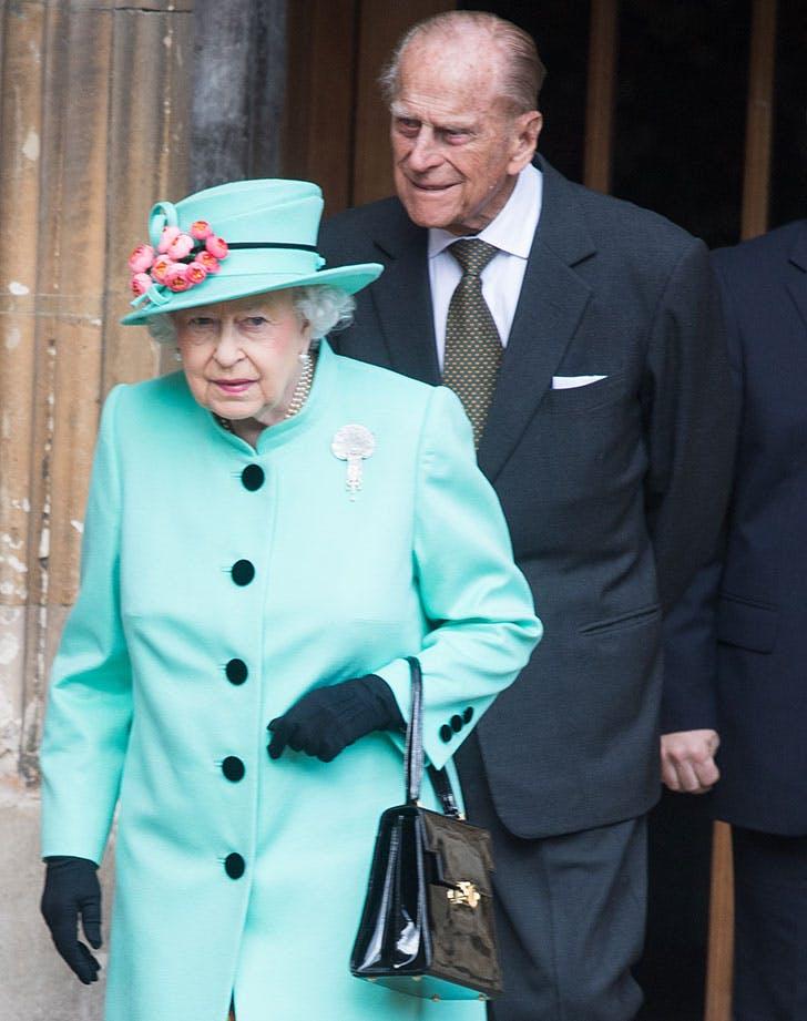 Queen Elizabeth II walks in front of Prince Philip