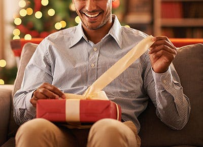 Shot of a handsome young man opening a christmas present 400