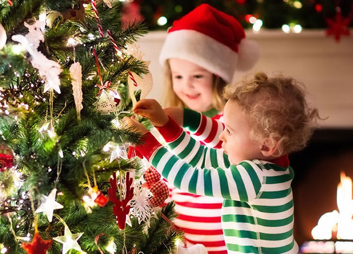 Swedish kids decorating Christmas tree in beautiful living room