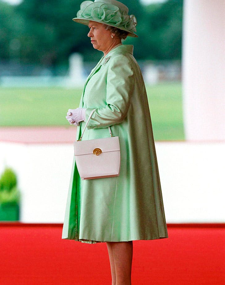 The Queen standing with her purse