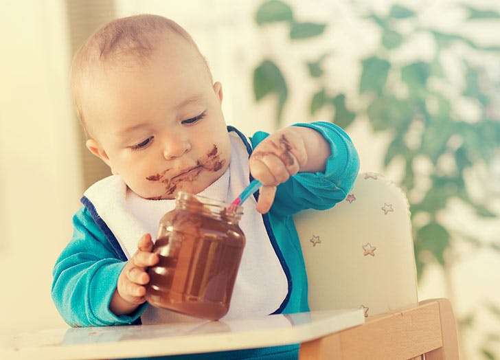 Baby boy eating chocolate out of jar