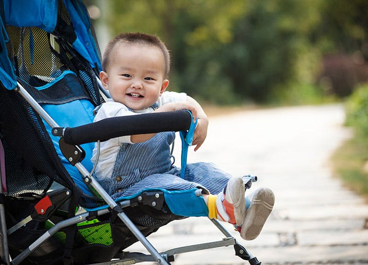 Baby boy sitting and smiling in stroller