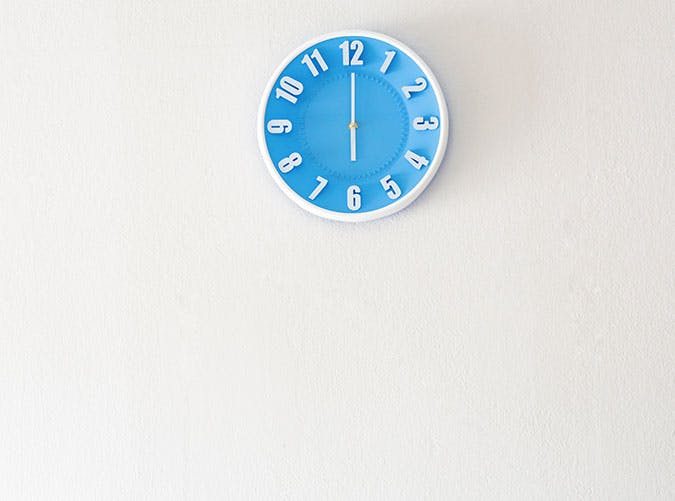 Bright blue clock on the wall showing 6 oclock