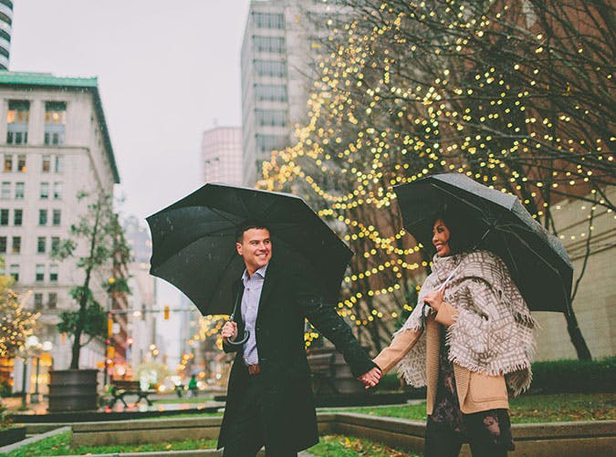 Couple holding hands and walking around outside in the rain