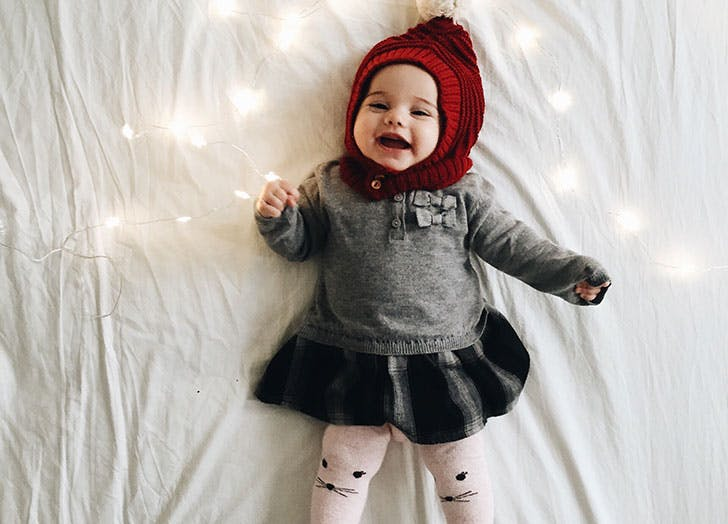 Cute Danish baby girl dressed up for winter lying on bed