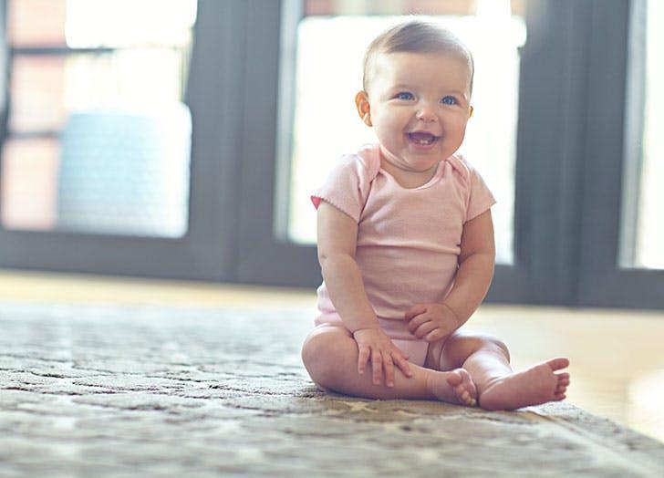 Cute baby girl sitting on floor