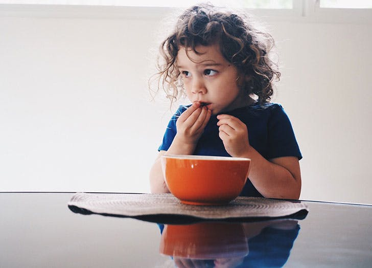 Cute kid eating food out of a bowl