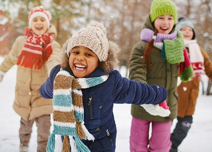 Cute kids running around in snow in December