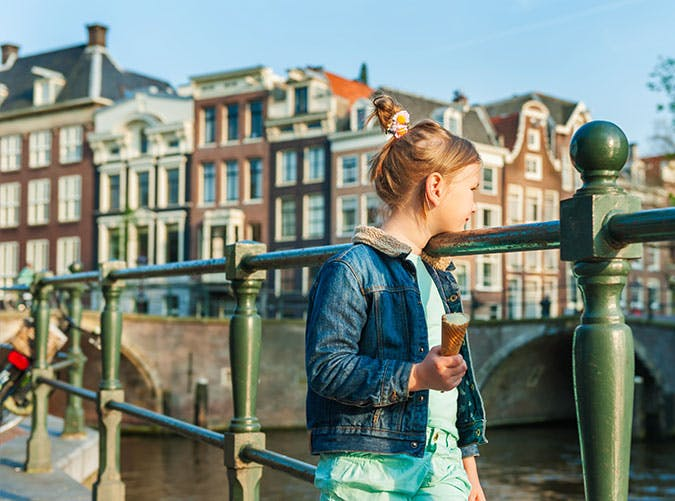 Cute little girl looking on a beautiful canal in Amsterdam Netherlands