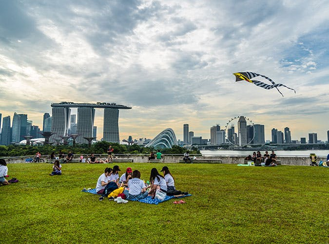 Families sitting in park looking at Singapore city skyline