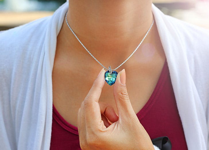 Female hand holding crystal pendant of December birthstone