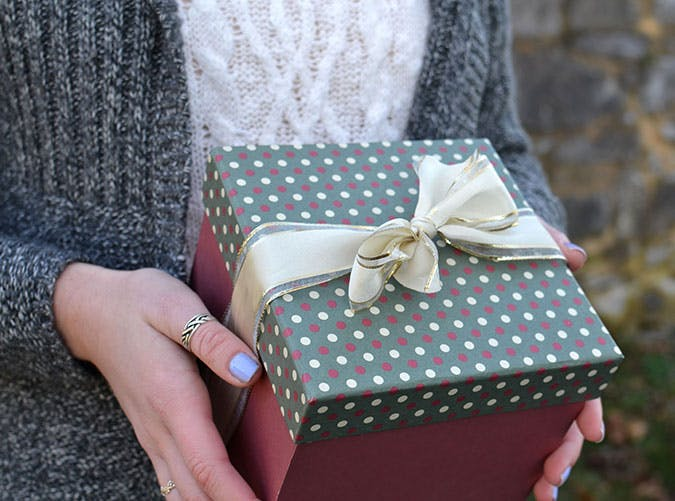Female holding a Christmas present or gift with a bow on it