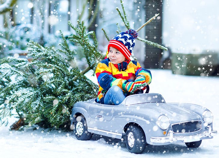 Funny little smiling kid boy driving toy car with Christmas tree
