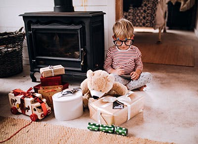 Kid playing on floor in living room with Christmas gifts 400
