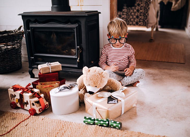 Kid playing on floor in living room with Christmas gifts