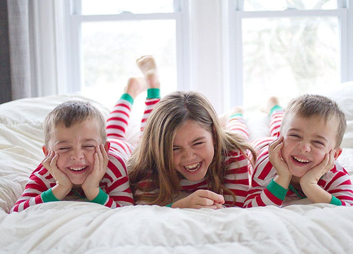 Kids on bed in Christmas pajamas laughing1