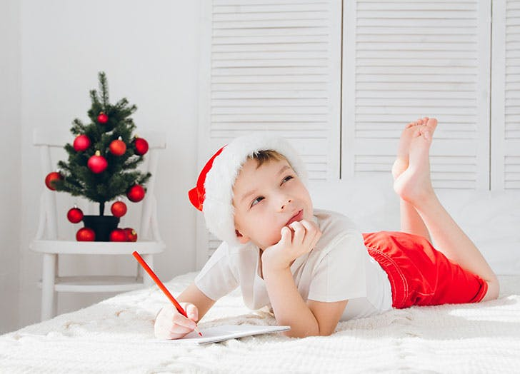 Little boy lying on bed writing Christmas thank you card