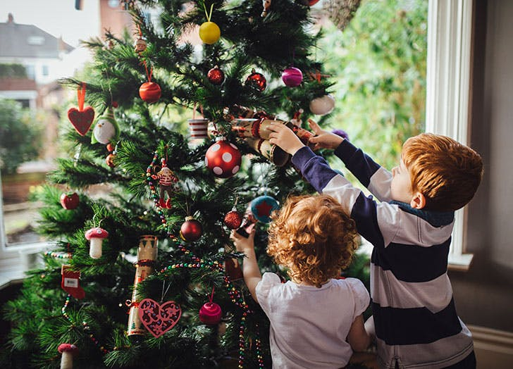 Two cute kids decorating Christmas tree indoors