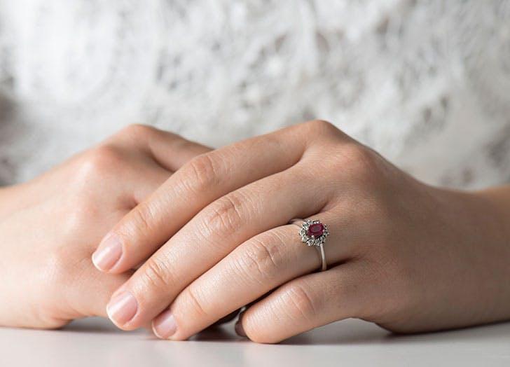 Woman and garnet January birthstone diamond ring