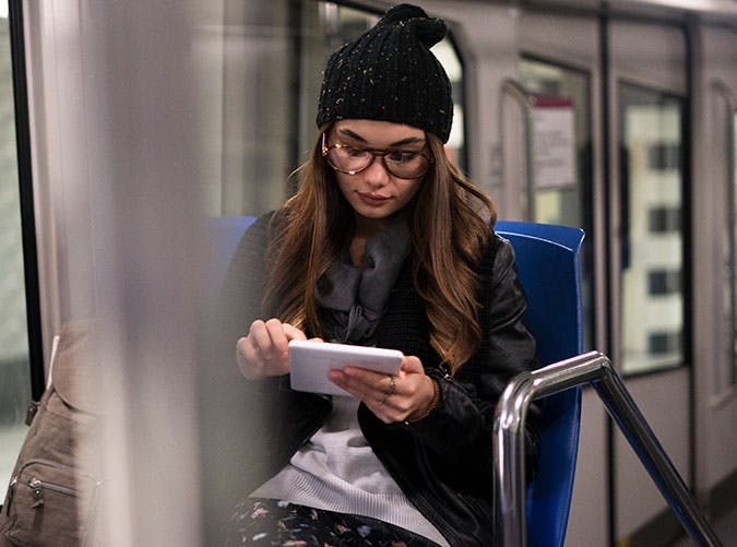 Woman reading a book on her kindle on subway