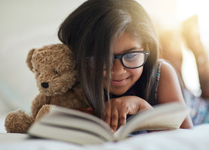 Young girl reading a book with a teddy bear