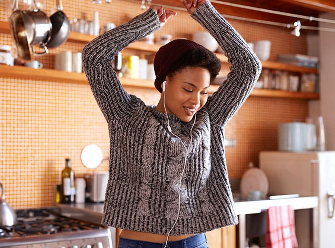 Young woman listening to music and dancing in kitchen