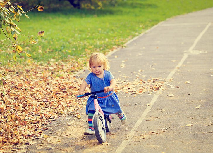 cute little girl riding runbike in autumn