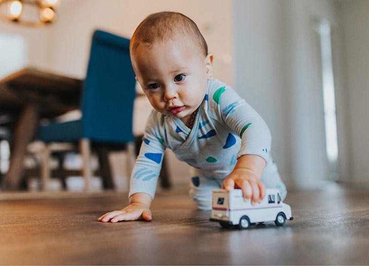 Baby boy playing on floor with toy truck