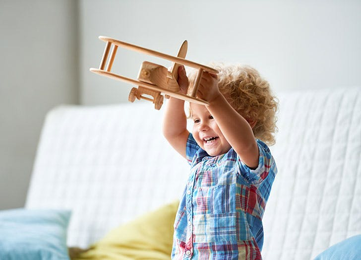 Cute kid playing with toy airplane