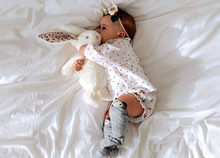 Norwegian baby girl Solvig lying in bed with stuffed animal