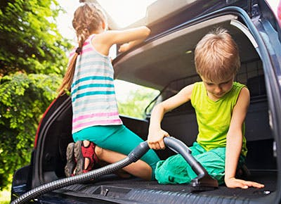 Two kids doing household chores cleaning the car 400