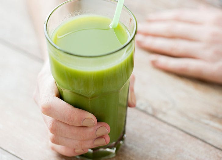 Woman holding green juice glass