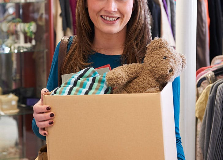 Woman taking box to charity shop