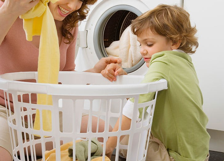 Young boy doing chores and laundry at home