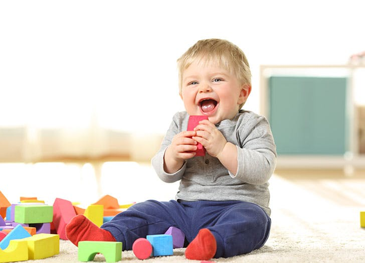 Baby playing on floor with toys