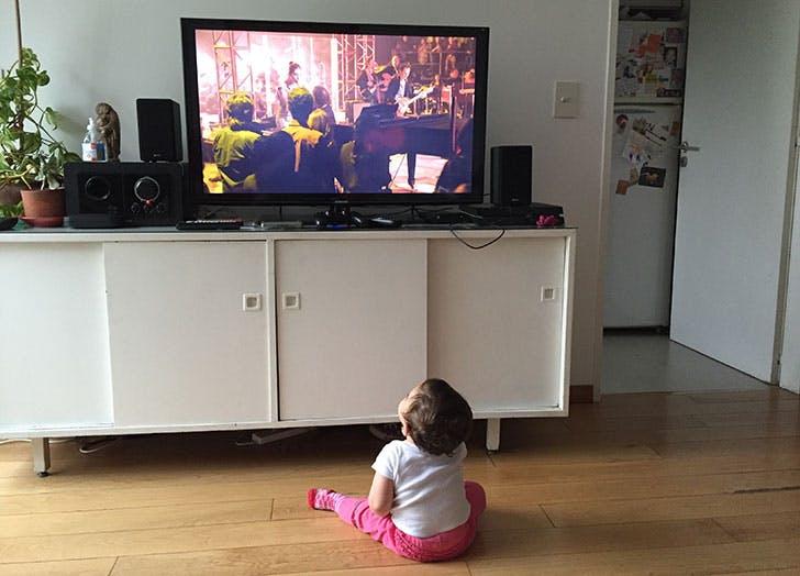 Baby watching TV on floor