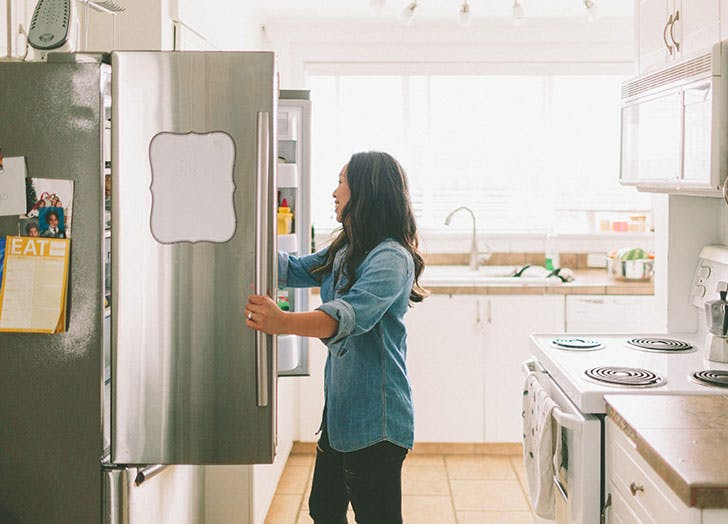 Woman opening up kitchen fridge